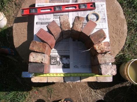 (Trazando el arco de ladrillo para hacer una forma de cartón, estableciendo los ladrillos en el molde de cartón).